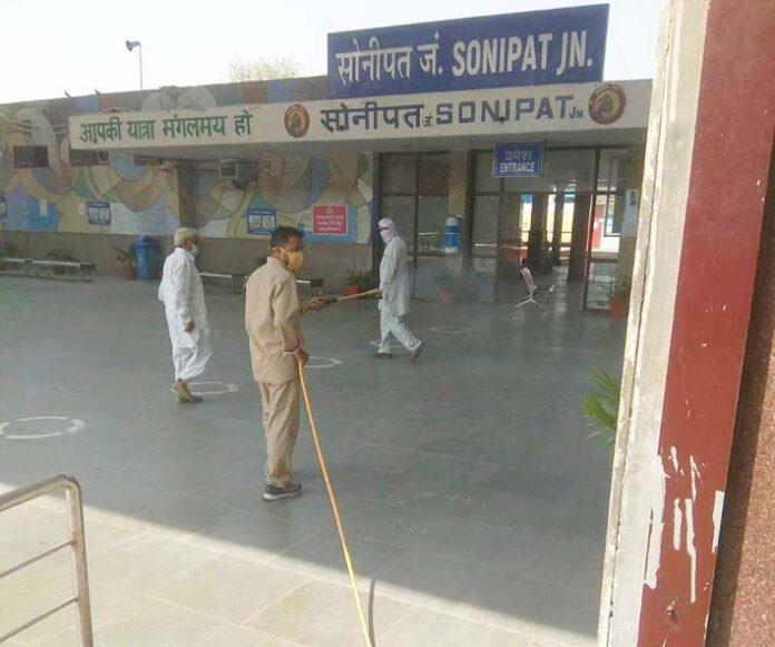 सोनीपत। रेलवे स्टेशन को सेनिटाइज करता कर्मचारी।